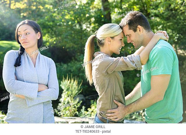 Couple and unhappy woman in forest