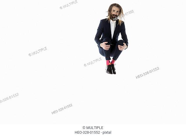 Portrait businessman jumping, hugging knees against white background