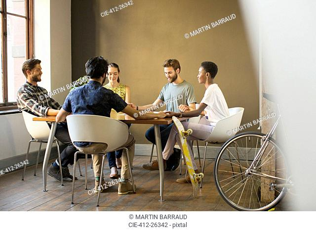 Creative business people holding hands at table in meeting