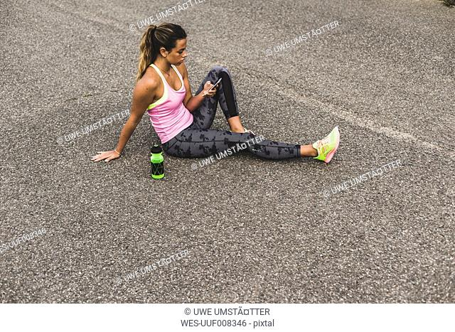 Sportive young woman sitting on street with cell phone and drinking bottle