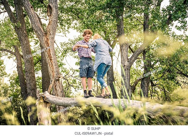 Young man with girlfriend balancing together on fallen tree