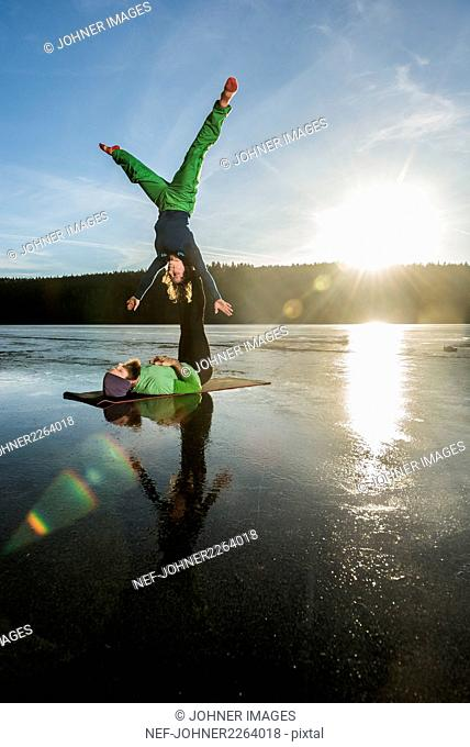 Couple doing yoga on frozen lake