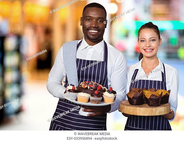 Restaurant owners with cakes against blurry background