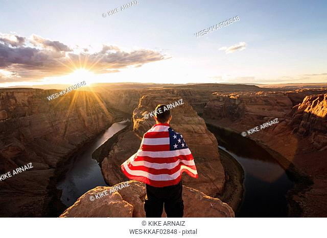 USA, Arizona, Colorado River, Horseshoe Bend, young man on viewpoint with American flag