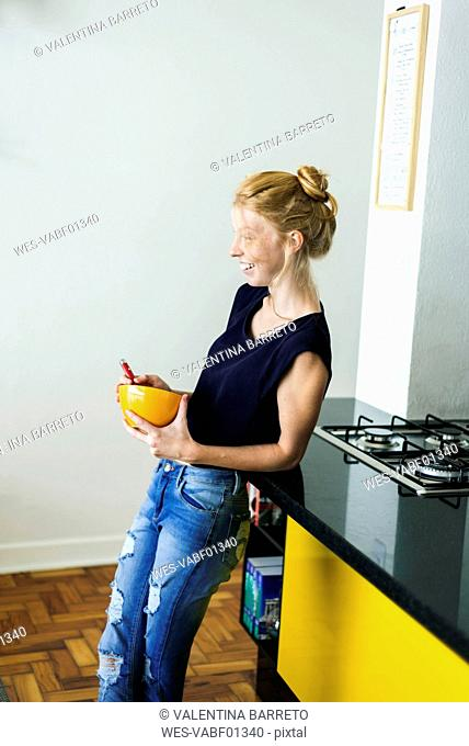 Ginger woman standing in kitchen eating breakfast