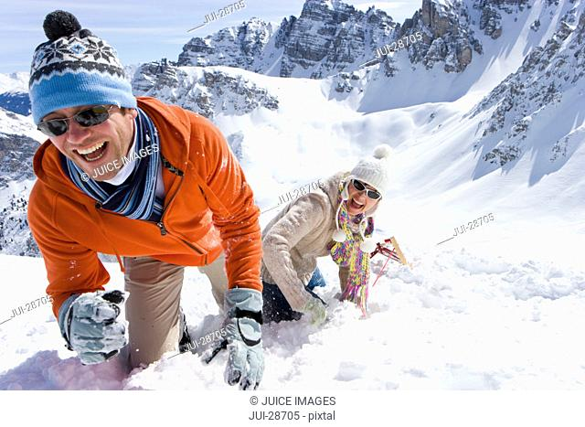 Smiling couple with sled climbing hill with mountain in background