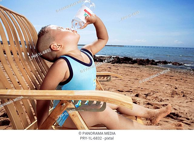 Boy drinking mineral water on beach