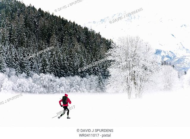 A jogger running through a snowy mountain landscape