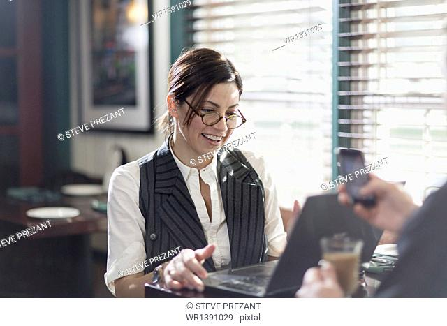 A woman seated at a desk, working over lunch. Using a laptop and mobile