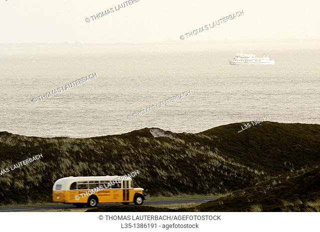 Ancient bus on Sylt, a ferry to Denmark in the background on the North Sea, Germany