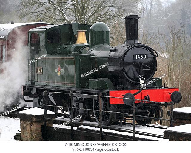 One of Britain's smaller locomotives, No. 1450 0-4-2 Tank engine waits just outside of a snowy Highley station on the Severn Valley Railway, Shropshire, England