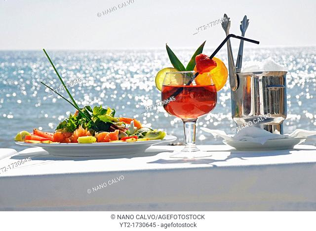 Cocktail and a fresh salad on the beach