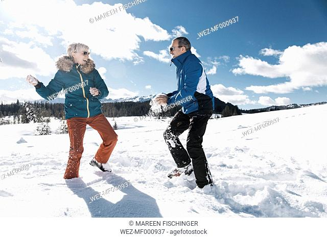 Germany, Bavaria, Winklmoosalm, Mature couple having a snowball fight