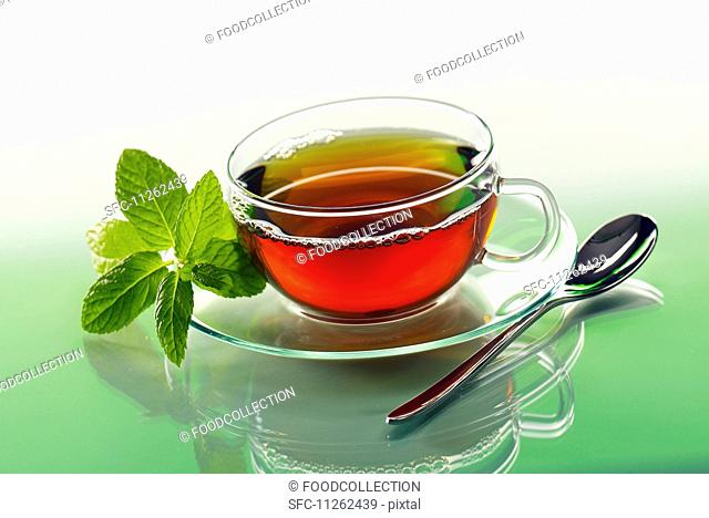 Peppermint tea in a glass cup with a sprig of fresh mint on the saucer