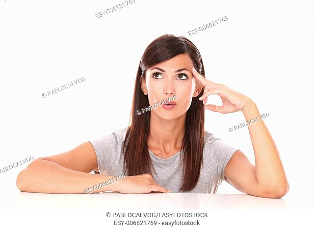 Portrait of reflective latin woman wondering while looking up on isolated white background - copyspace