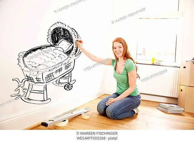 Young woman drawing a baby crib on a wall in new apartment