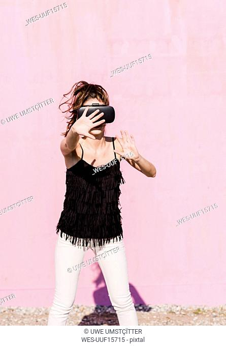 Young woman wearing VR glasses in front of pink wall