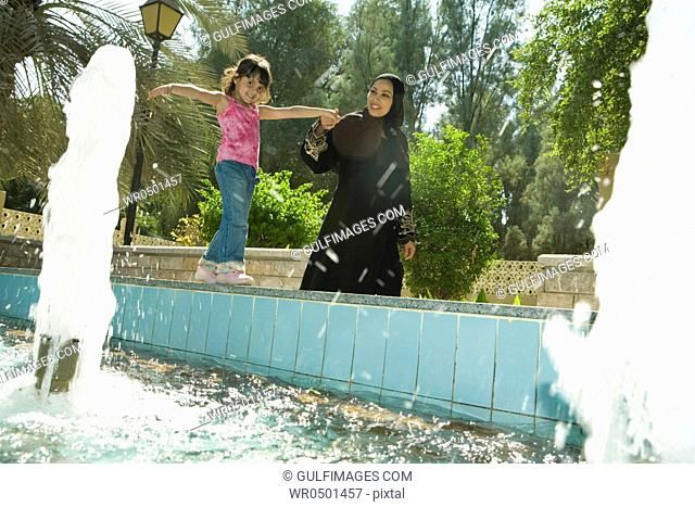 Mother with daughter standing by fountain at park, smiling