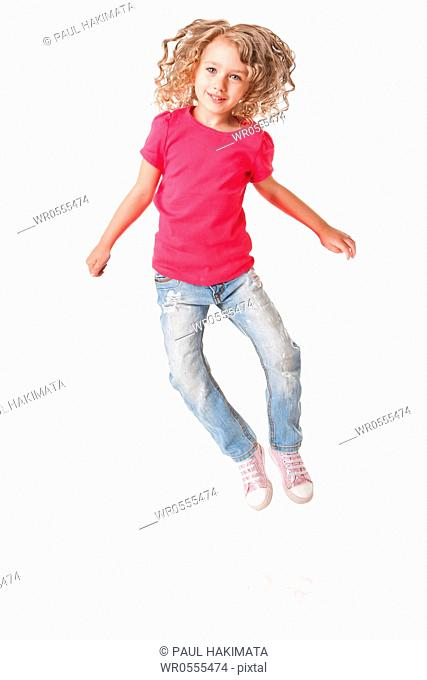 Cute happy smiling jumping of joy girl with heels together in pink shirt and jeans, isolated