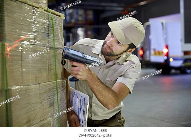 Truck driver worker with scanner scanning pallet of boxes in distribution warehouse