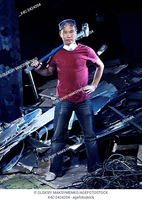 Portrait of a man with a sledgehammer doing renovations and demolition