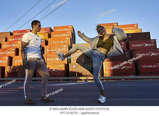 Australia, Adelaide, woman kicking food to man, in front of ship containers. Couple, Relationship, fight, controversial. Fashion Bloggers Reno Marrasso and...