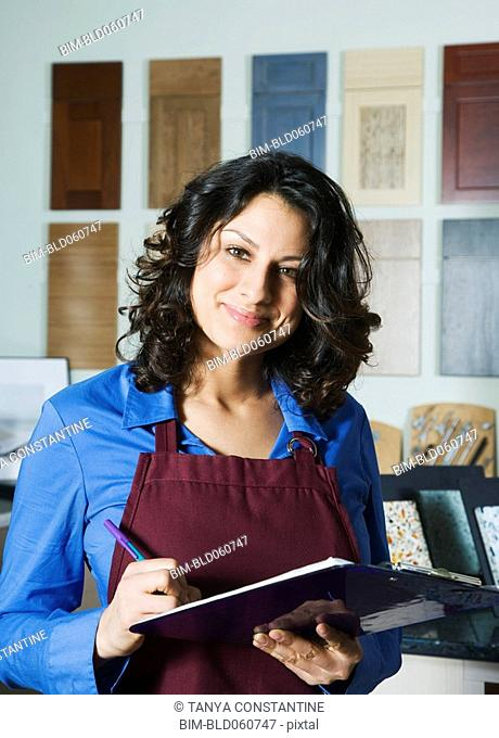 Hispanic sales clerk writing on clipboard