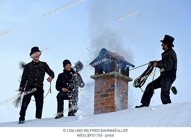 Three chimney sweeps working on roof top