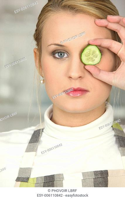 Woman hiding her eye with slice of cucumber