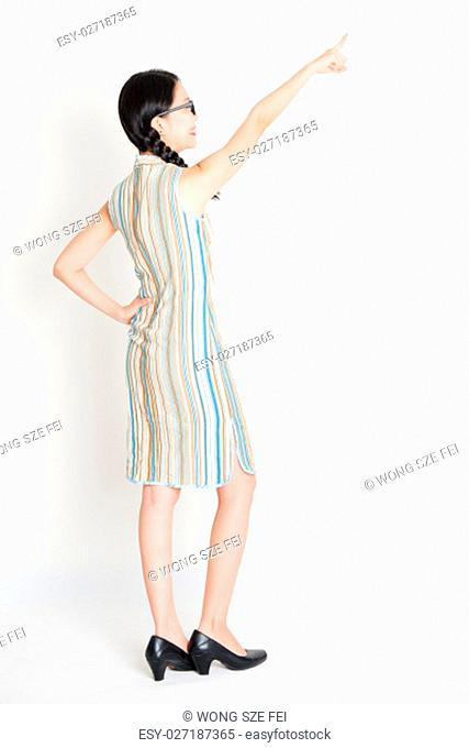 Rear view of young Asian girl in traditional qipao dress finger pointing away, full length standing on plain background
