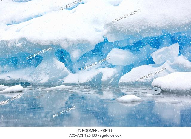 A grounded iceberg is slowly covered in snow from a summer storm near Pleneau Island, Pleneau Island, Lemaire Channel, Antarctic Peninsula
