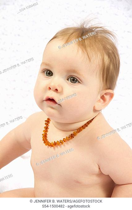 A caucasian baby boy indoors, 8 months old, wearing a baltic amber necklace for teething pain