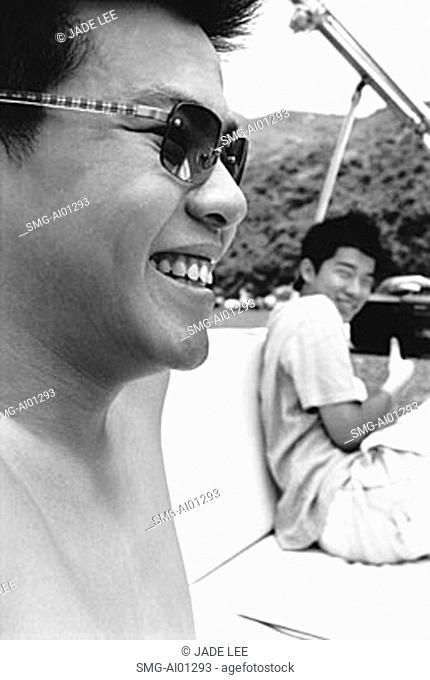 Teen boys in boat with sunglasses, smiling