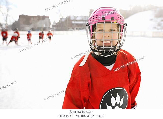 Portrait of smiling girl in ice hockey uniform