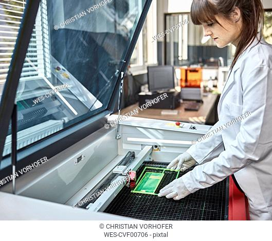 Female technician checking laser cutter in laboratory