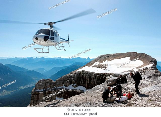 BASE jumpers preparing wingsuits on mountain summit, Dolomites, Italy