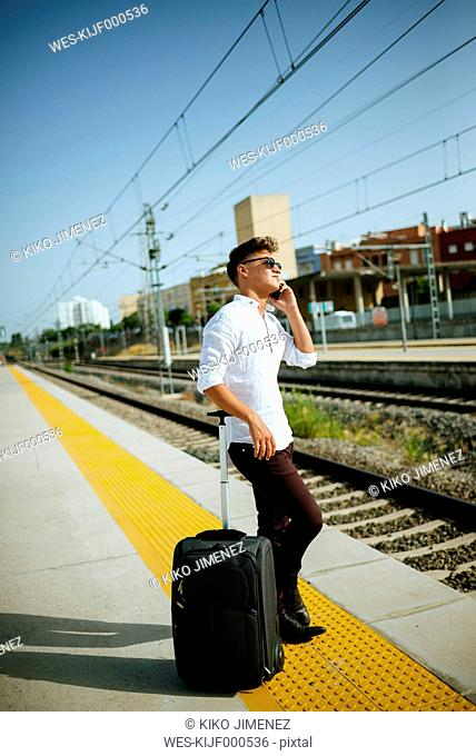 Young man on cell phone at station platform