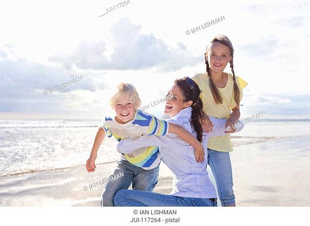 Mother Hugging Children On Beach Vacation Together
