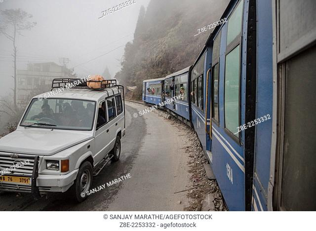 A TATA Sumo taxi on national highway 55 and the Darjeeling Himalayan railway (toy train) in Darjeeling, West Bengal, India