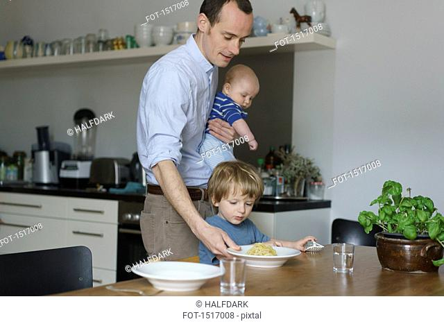 Father carrying toddler while giving food to son at dining table