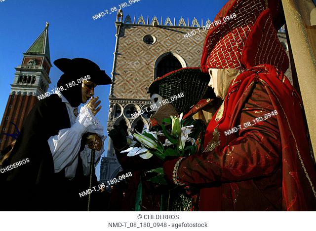 Masked performers in front of a palace, Doges Palace, Venice, Veneto, Italy