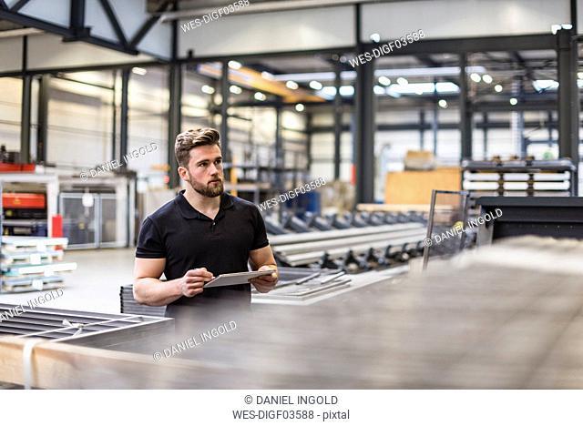 Man using tablet on factory shop floor