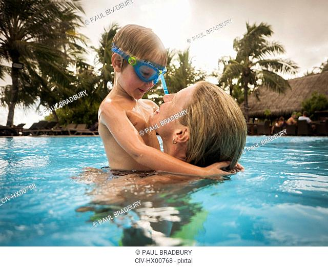 Mother and son hugging in swimming pool