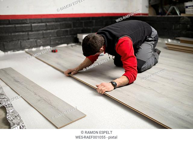 Young man placing a laminate floor