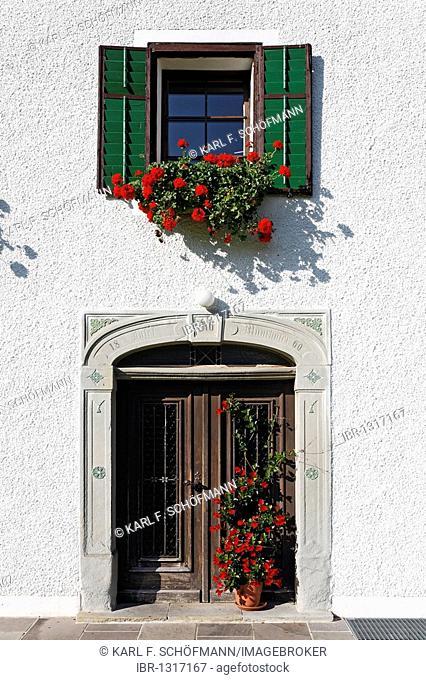 Old entrance portal and windows with geraniums, farmhouse from 1860, Mondsee Land region, Salzkammergut region, Upper Austria, Austria, Europe