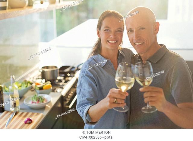 Portrait happy mature couple toasting white wine glasses, cooking in kitchen