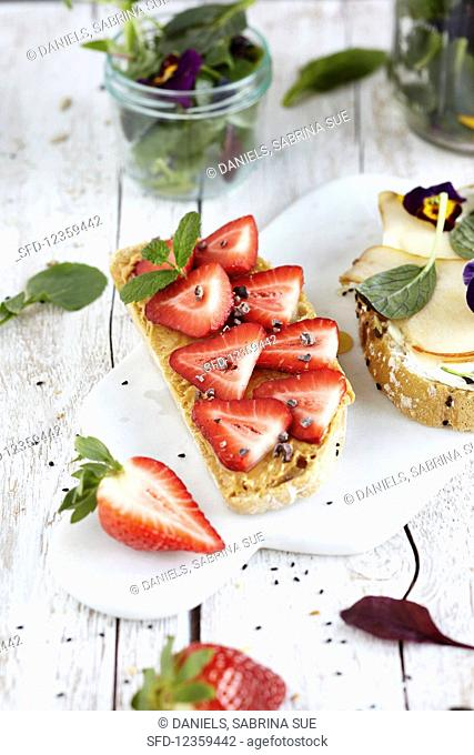 Open sandwiches topped with strawberries and peanut butter, and pear slices