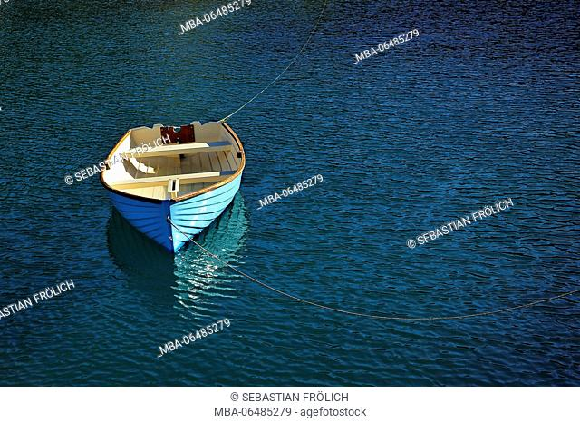 rowboat or sailboats with two ropes in the blue slightly wavy water fixed