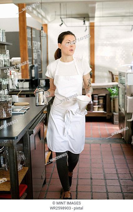 Woman wearing an apron walking along a corridor, carrying a coffee pot and filter