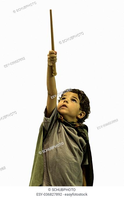 Child posing as a wizard with wand in hand